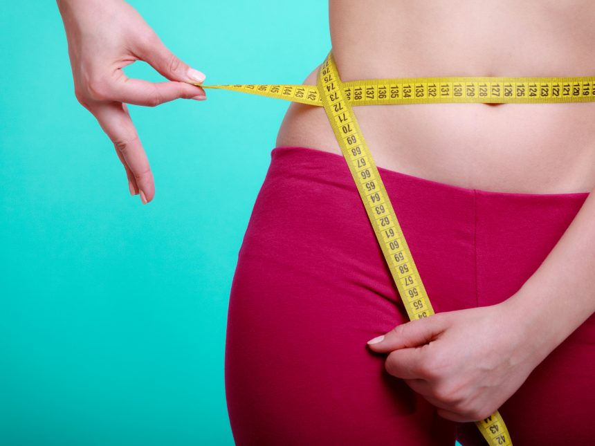 woman measuring waist - did you know that losing weight can boost immune system?